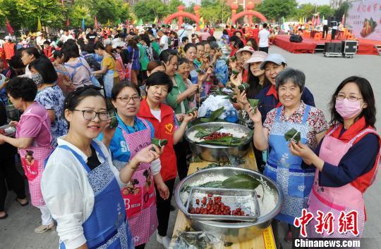图为参与包粽子的社区居民展示她们的劳动成果。 苑立伟 摄
