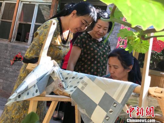 """每到农闲时节,村里的六七十位""""绣娘""""就开始忙碌起来。 王斌田摄"""