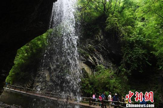 游客在瀑布下拍照留念。 杨艳敏 摄