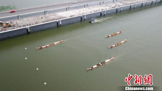 图为众多前来观赛的市民,他们在湖边为选手们呐喊助威。 孟德龙 摄