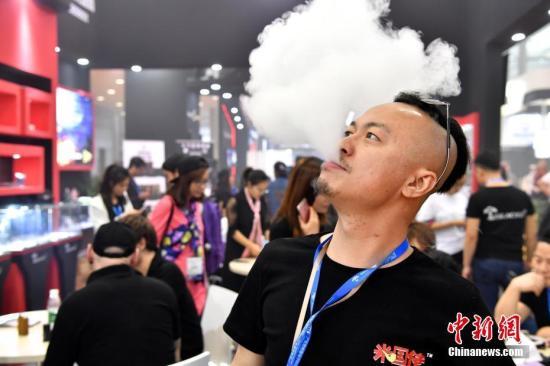 资料图片:工作人员演示电子烟吐雾。