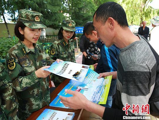 图为西藏自治区公安边防总队侦查支队邦锦梅朵女子办证室官兵在为民众发放宣传资料。 西藏自治区公安边防总队供图 摄