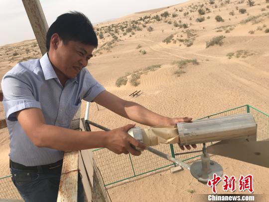 图为甘肃省治沙研究所民勤野外观测站副站长郭树江在沙尘暴观测塔上采集数据。 艾庆龙 摄