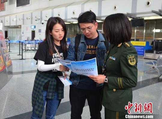 图为西藏公安边防官兵在向旅客介绍《西藏自治区边境管理区通行证管理实施办法》。 西藏自治区公安边防总队供图 摄