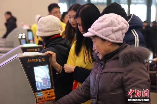 """资料图:2018年2月1日,哈尔滨火车站,旅客手持身份证和车票自助式通过实名制验票通道,获得无障碍""""刷脸""""进站体验。<a target='_blank' href='http://www.chinanews.com/' _fcksavedurl='http://www.chinanews.com/'></p><p>中新社记者于琨摄"""