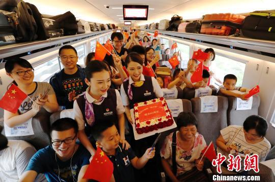 """长编组""""复兴号""""动车组,列车员与旅客庆祝这一时刻。 殷立勤 摄"""