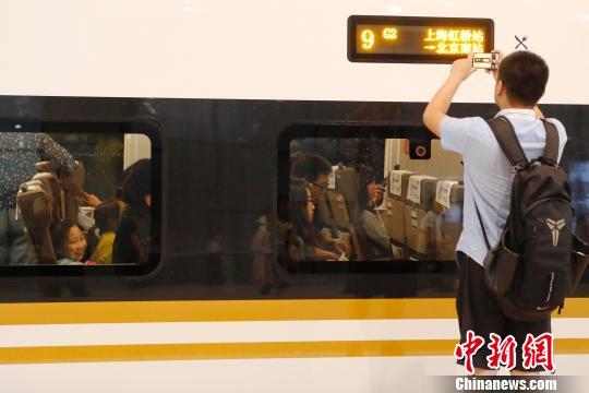 """长编组""""复兴号""""动车组正式运营,旅客用手机记录下这一历史性时刻。 殷立勤 摄"""