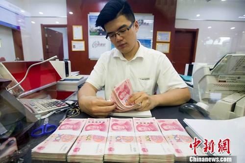 资料图:银行工作人员正在清点货币。<a target=