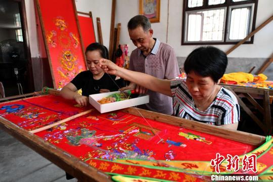 他与妻子在村中开办了一家刺绣家庭作坊,制作寿序、龙伞、迎神旗等民俗活动类刺绣用品。吕明 摄 吕明 摄