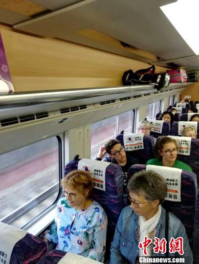 图为外国游客搭乘昆楚大铁路动车。 中国铁路昆明局集团有限公司供图 摄