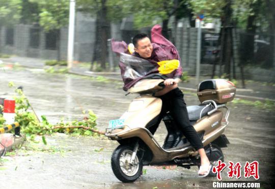 图为路人艰难骑行。 王东明 摄