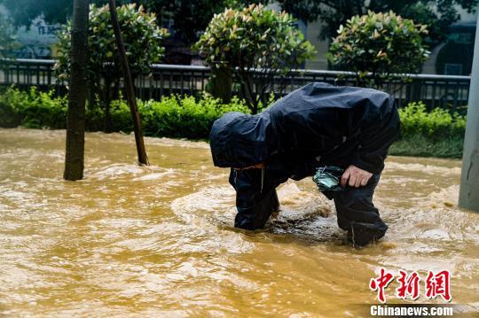 断枝树叶堆积在雨水篦子外导致排水不畅,工作人员徒手清理雨水篦子,确保排水通畅。成都市城管委