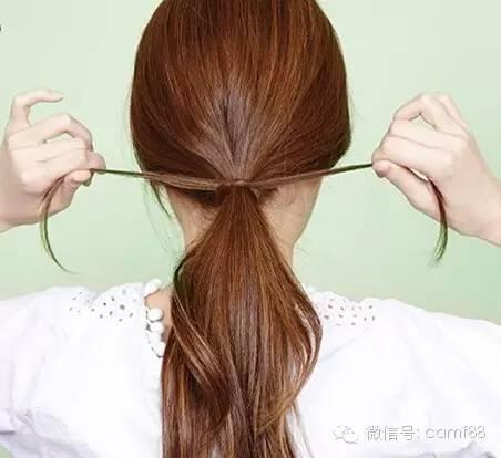 步骤二:从马尾中取出两小束头发,缠绕着辫子底部一圈后交叉打结