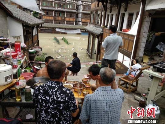 图为洪水涌进铜梁安居镇,市民在高处避险。 陈钢 摄