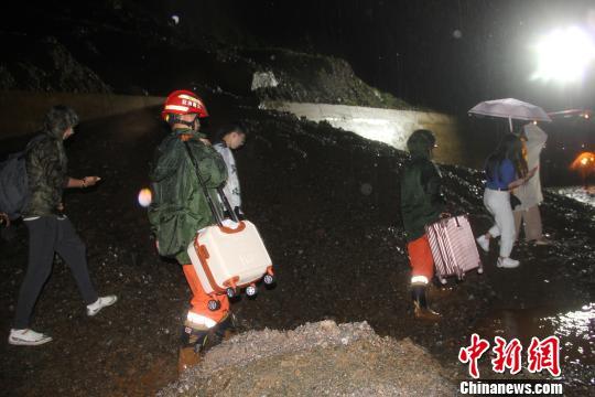 图为消防官兵帮助被困人员转移行李 唐国松 摄