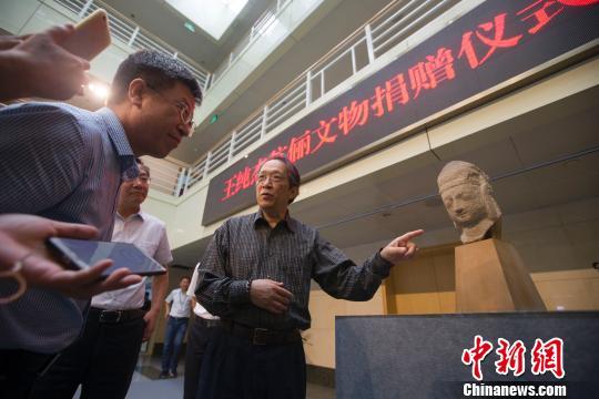 美籍华裔王纯杰向媒体介绍石雕天王像收藏经历。 张云摄