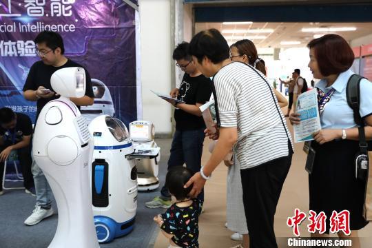 """市民们与机器人""""小胖""""进行互动。 胡耀荣 摄"""