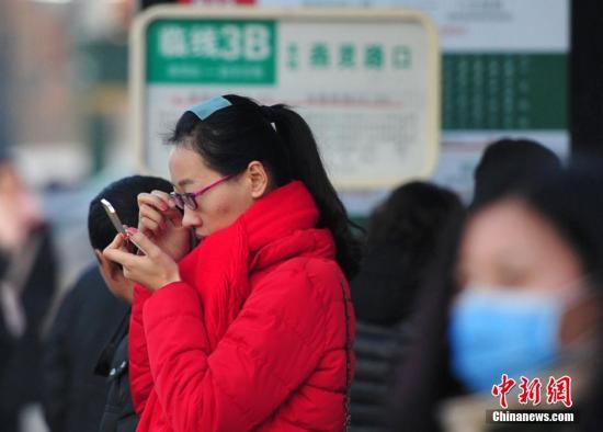 资料图:等待公交的女市民化妆,整理面容。 翟羽佳 摄