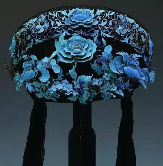 据说,翠羽必须从活的翠鸟身上拔取,才可保证颜色之鲜艳华丽,翠羽根据部位和工艺的不同,可以呈现出蕉月、湖色、深藏青等不同色彩,点翠的羽毛以翠蓝色和雪青色为上品,加之鸟羽的自然纹理和幻彩光,整件作品富于变化,富丽堂皇又不失生动活泼。