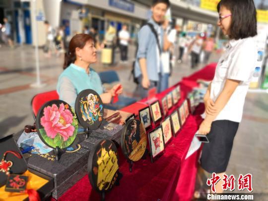 """7月13日,中国铁路兰州局集团有限公司和甘肃各地旅行社联合启动""""环西部火车游'1+6+N'""""精品线路游。图为在列车上展示的旅游文创产品。 丁思 摄"""