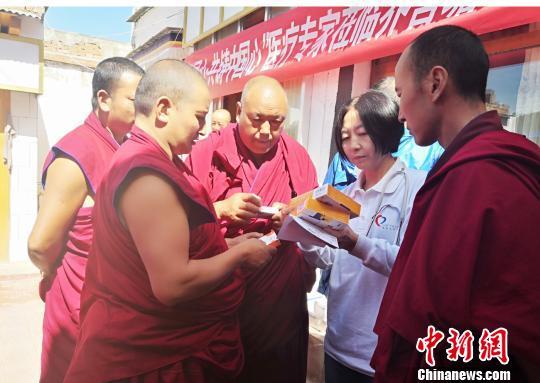 图为专家为僧人叮嘱服药注意事项。 南如卓玛 摄