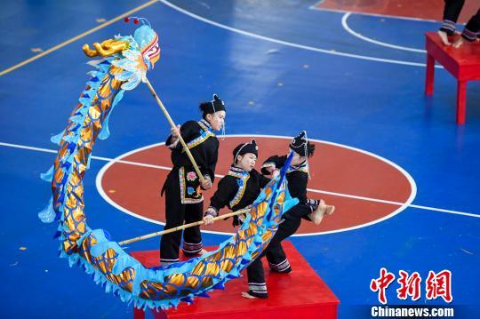 华侨大学的大学生身着畲族服饰在狭小的方桌上舞起了三人龙。 杨华峰 摄