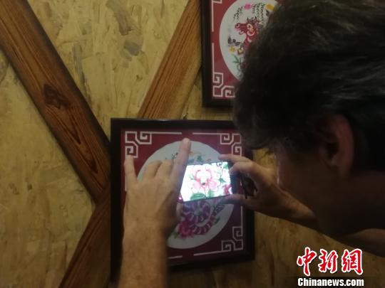 7月13日,在位于江西上饶市横峰县的中国剪纸文化展示馆,奥利维???戈舒??对于中国的剪纸艺术产生极大的兴趣。图为奥利维???戈舒??用手机拍摄剪纸作品。 苏路程 摄