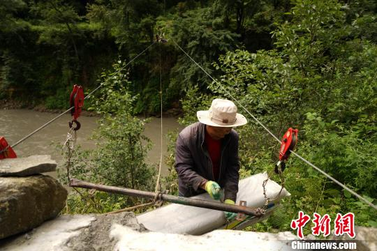 图为当地农牧民通过过江索道运输茶田所需的农用物资。 江飞波 摄