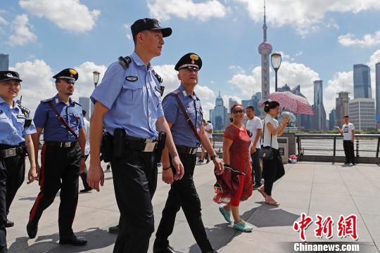 """18日,由2名意大利警员和2名上海公安民警编为一组在上海外滩进走说相符巡逻,""""中西相符璧""""的画面引来不少市民游客益奇的现在光。 殷立勤 摄"""