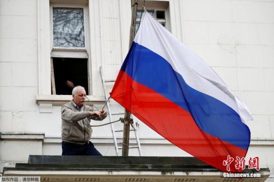 资料图:当地时间2018-07-24,一名男子将俄罗斯驻英国大使馆门前的俄罗斯国旗取下。英国首相特蕾莎?梅此前宣布,将驱逐23名俄罗斯外交官。此外,还将冻结俄罗斯在英国的国有资产。 近日,俄罗斯前情报人员斯克里帕尔与其女儿在伦敦某商场内接触不明物质后当场倒下。随后,这一事件引发英俄外交风波。