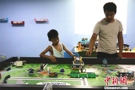 广西柳州市一机器人兴趣班内,老师正在教学生制作机器人。 林馨 摄