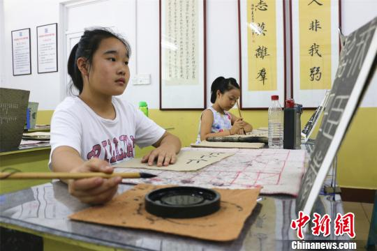 广西柳州市一书法兴趣班里,学生正在认真写毛笔字。 林馨 摄
