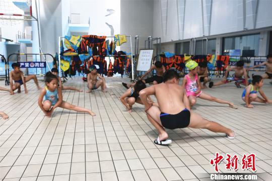 广西柳州市游泳馆内,孩子下水游泳前在岸上做热身运动。 林馨 摄