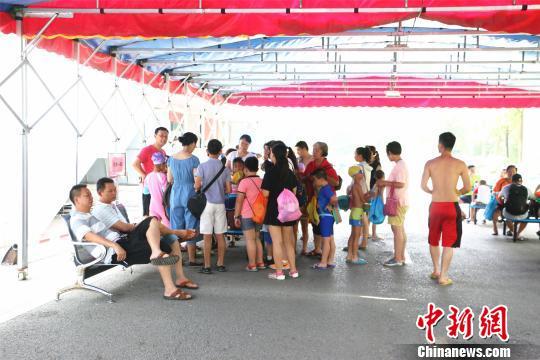 广西柳州市游泳馆外,站满排队帮孩子报名上兴趣班孩子的家长。 林馨 摄