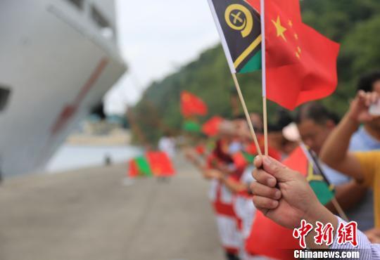 华人华侨挥动中瓦两国国旗在码头欢迎。 史奎吉 摄