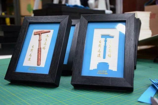 锤柄采用云纹图案,浮雕效果,锤头的一侧,刻有北京工业大学的标志,另图片