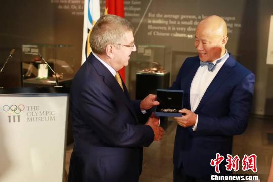 国际奥委会主席巴赫向吕俊杰赠送纪念品。主办方供图