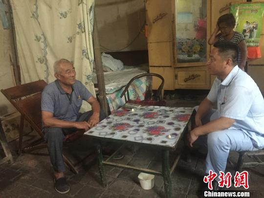 """图为""""家庭病床""""医生王炳坤为邢怀信上门诊疗。 郝烨摄"""