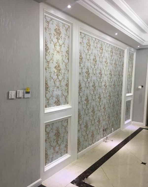 电视背景墙是用石膏板打造的造型框,里面贴的是素色花纹壁纸,效果优雅