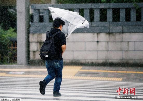 资料图:市民在雨天出行。