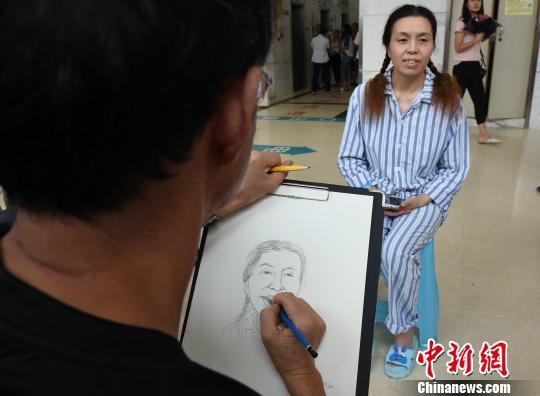 图为漫画家走进医院为患者画漫画肖像图。 周毅 摄