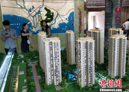 资料图:购房者在三亚一售楼处看沙盘。 王晓斌 摄
