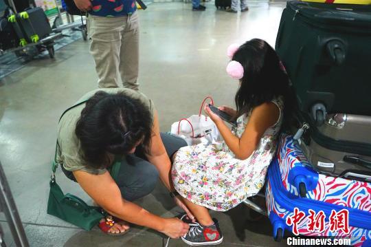 候机厅外不少滞留旅客将行李放在手推车上,靠着休息。 关向东 摄