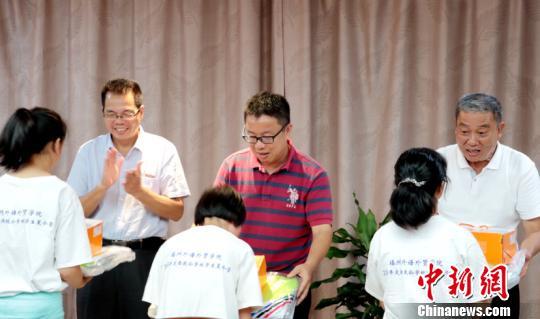 活动现场,与会领导向致公学校的师生们赠送学习礼品。 陈屹 摄
