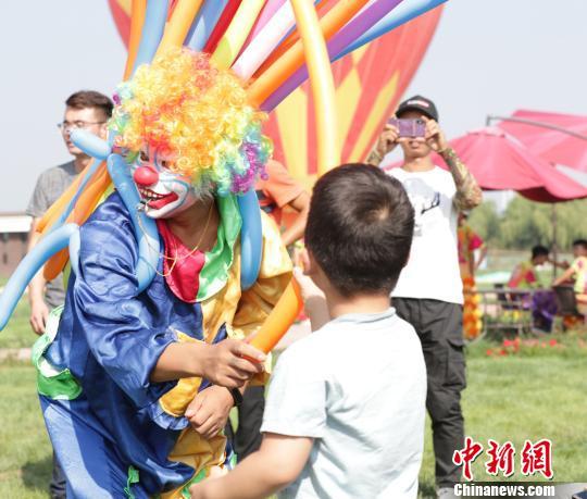 小丑正在与小同伙互动。 杨迪 摄