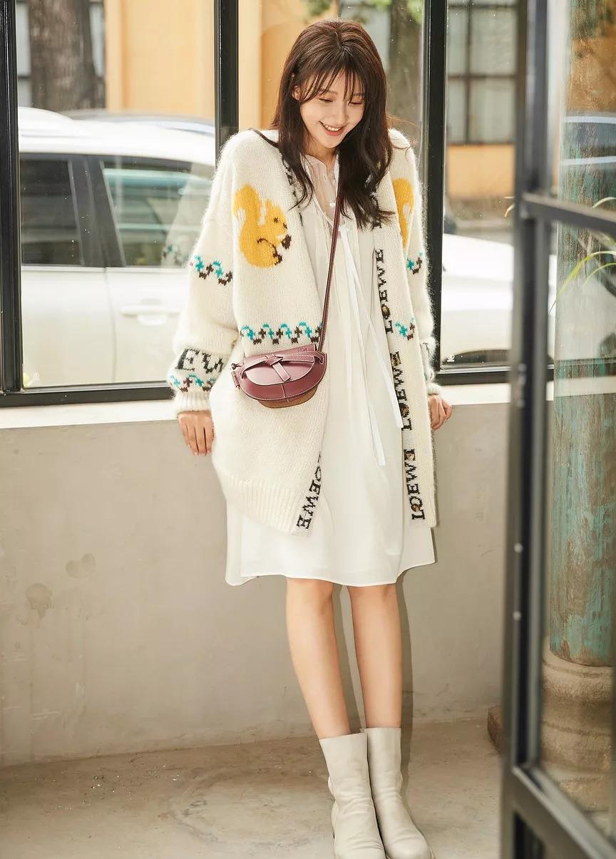 孙怡身穿针织开衫搭配白色连衣裙,温婉动人,又不失活泼俏皮.