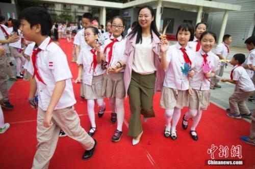 资料图:教师节,老师们牵着学生的手走过红地毯步入校园。张云摄