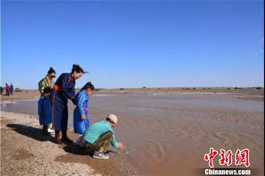 图为当地牧民水边嬉戏。 额济纳旗委宣传部供图摄