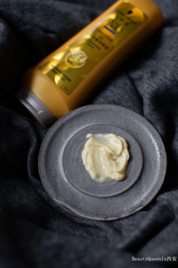 然后在清洗干净的头发上打上润发乳,乳黄色的发乳像护肤精华般水润不