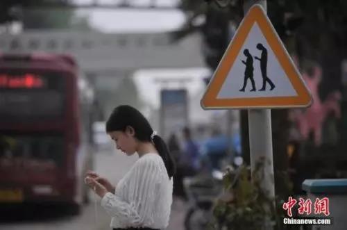 """资料图:重庆一红绿灯处摆放""""不做低头族、关注红绿灯""""警示牌。 陈超摄"""